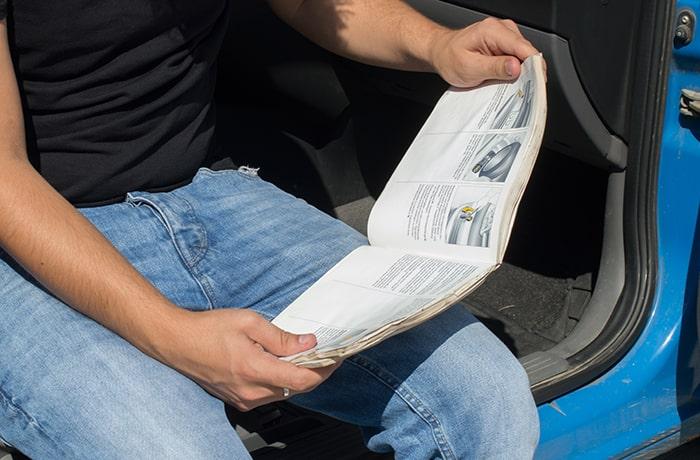 Человек читает инструкцию к машине